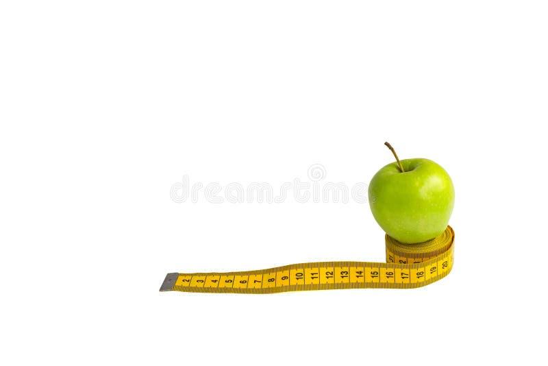 Зеленое яблоко и измеряя лента с сантиметрами и дюймами изолированные на белой предпосылке стоковое фото rf