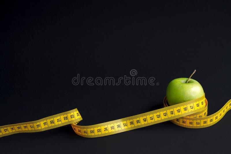 Зеленое яблоко и измеряя лента с сантиметрами и дюймами изолированные на черной предпосылке стоковая фотография rf