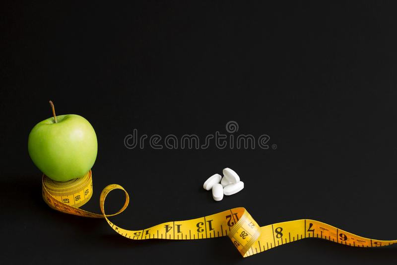 Зеленое яблоко и измеряя лента с сантиметрами и дюймами изолированные на черной предпосылке стоковые изображения