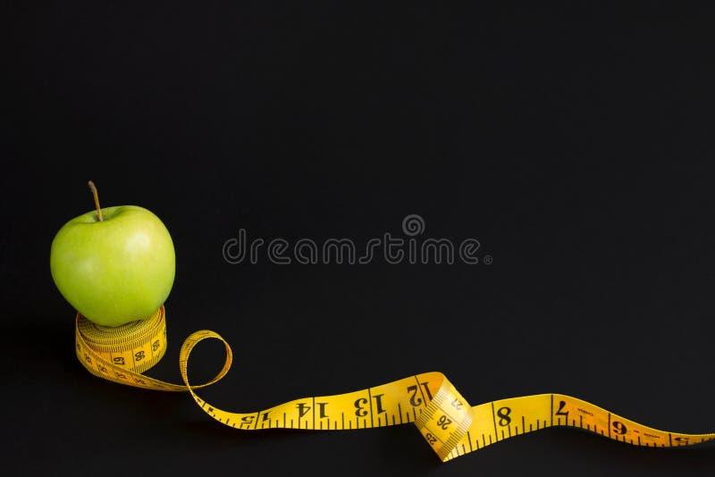 Зеленое яблоко и измеряя лента с сантиметрами и дюймами изолированные на черной предпосылке стоковые фотографии rf