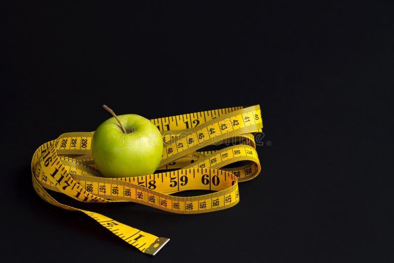 Зеленое яблоко и измеряя лента с сантиметрами и дюймами изолированные на черной предпосылке стоковые изображения rf