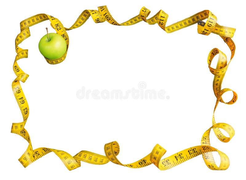 Зеленое яблоко и измеряя лента с сантиметрами и дюймами как рамка изолированная на белой предпосылке стоковое изображение rf