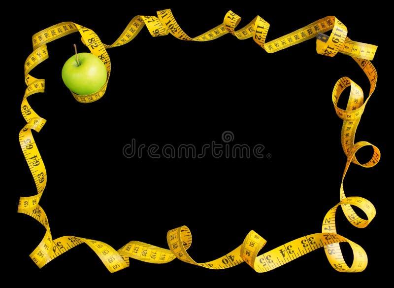 Зеленое яблоко и измеряя лента с сантиметрами и дюймами как рамка изолированная на черной предпосылке стоковое изображение