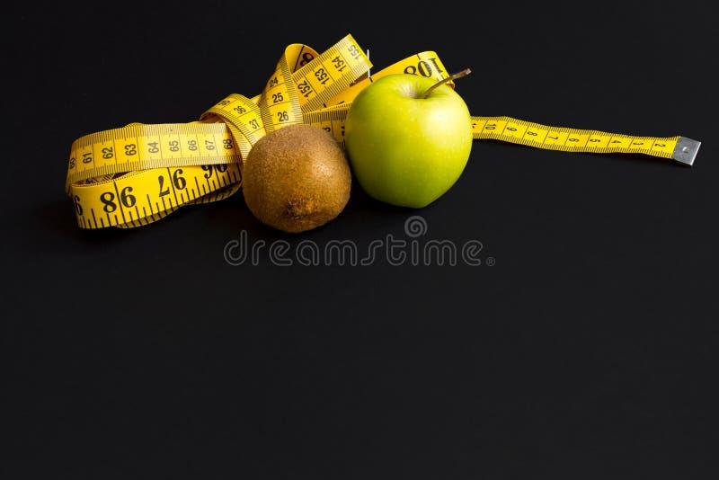 Зеленое яблоко, киви и измеряя лента с сантиметрами и дюймами изолированные на черной предпосылке стоковая фотография