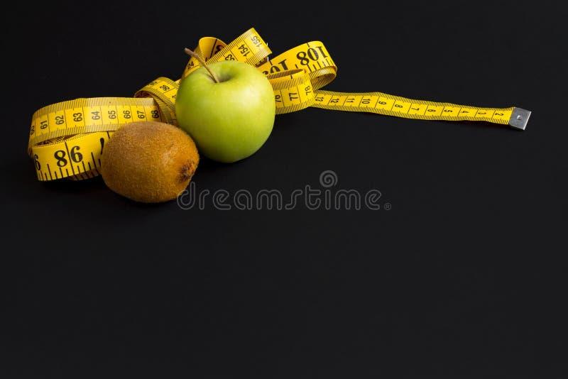 Зеленое яблоко, киви и измеряя лента с сантиметрами и дюймами изолиров стоковое изображение