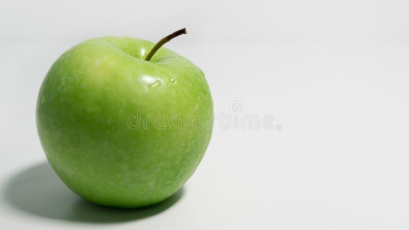 Зеленое яблоко на белой предпосылке с космосом, который нужно выпрямить стоковые изображения