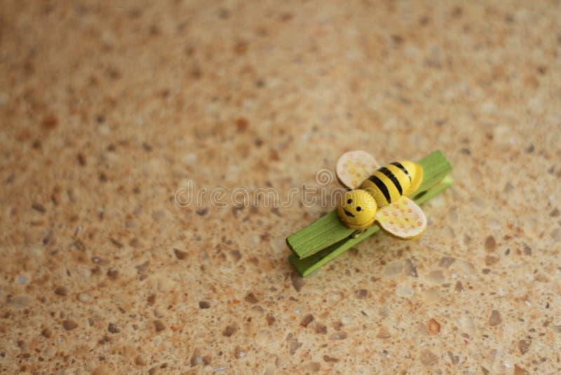 Зеленое clothespeg в форме желт-черной пчелы на пестротканой красной предпосылке стоковые фото