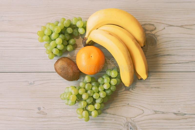 Зеленые виноградины, плод кивиа и апельсин в теплых солнечных цветах на деревянной предпосылке стоковые фотографии rf