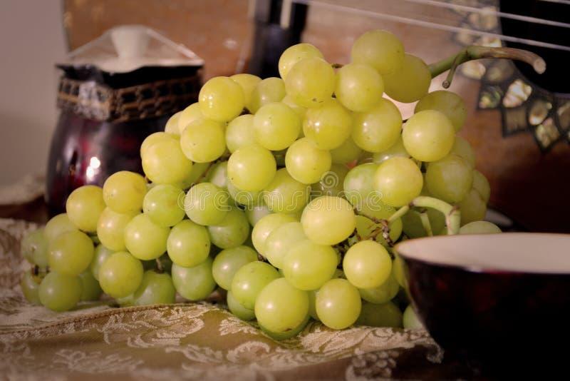 Зеленые виноградины с гитарой на предпосылке стоковые фотографии rf