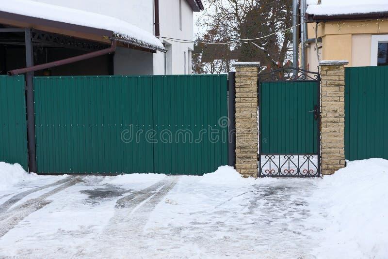Зеленые ворота металла и обнести забором белые смещения снега на улицу зимы стоковые изображения