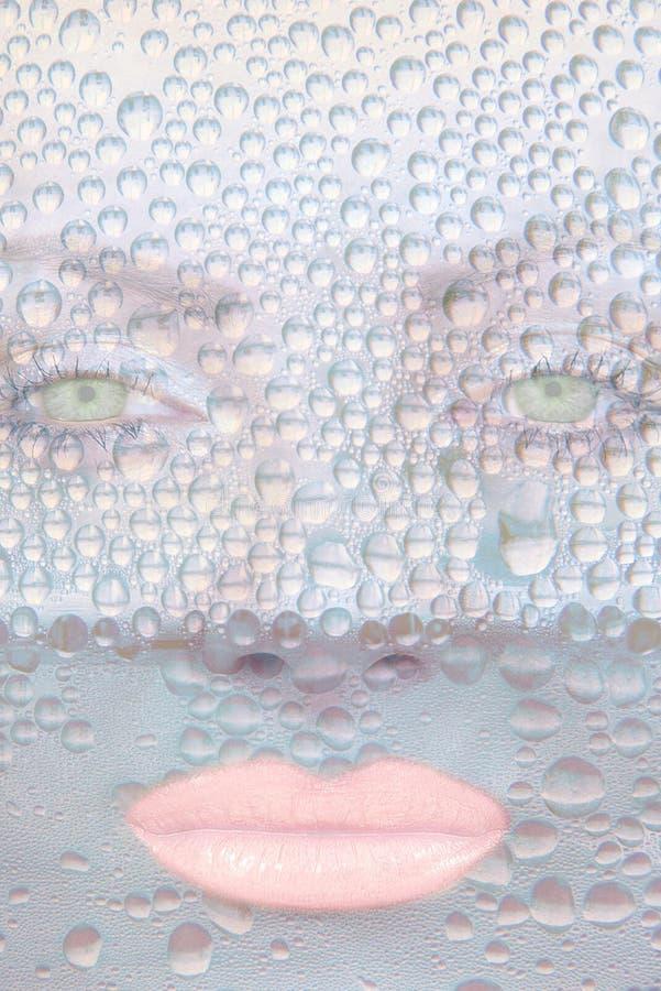 Зеленые глаза девушок против прозрачных падений воды стоковые фото