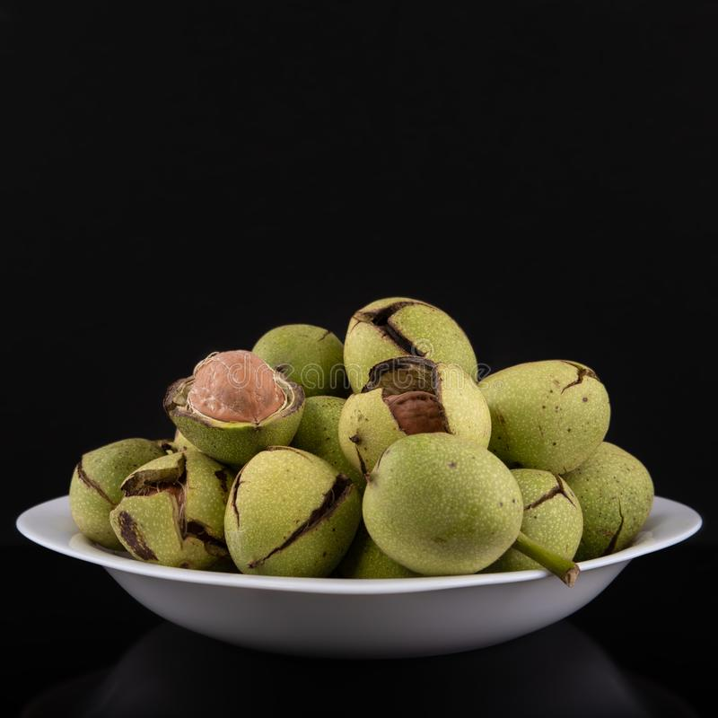 Зеленые грецкие орехи в плите на черной предпосылке, треснутая корка, свежий стержень стоковые изображения