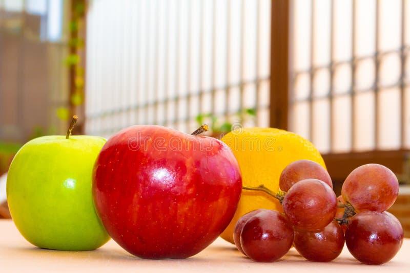 Зеленые и красные яблоки, виноградины и апельсин стоковые фото