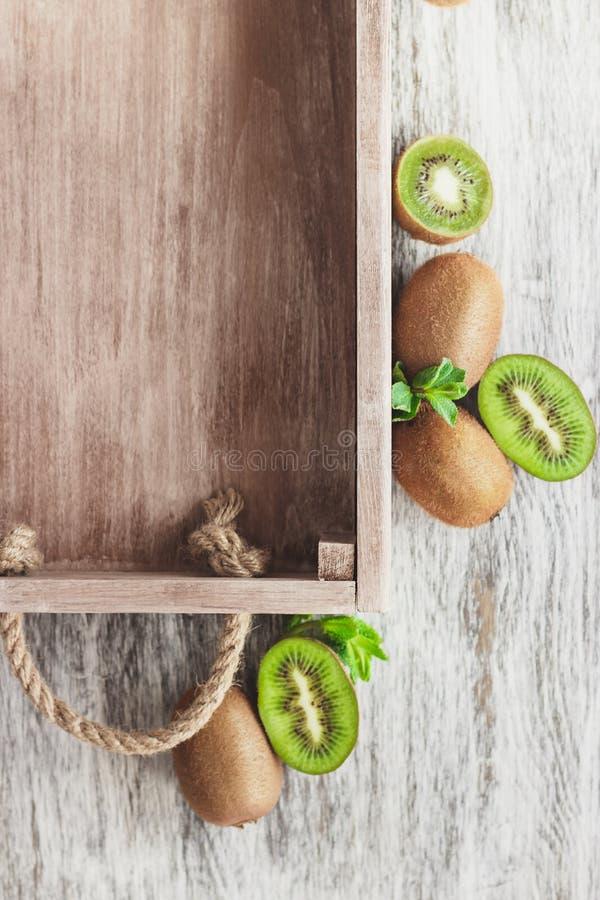 Зеленые кивиы и листья мяты в деревянном подносе стоковое изображение rf