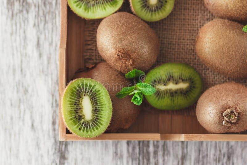 Зеленые кивиы и листья мяты в деревянном подносе стоковые изображения