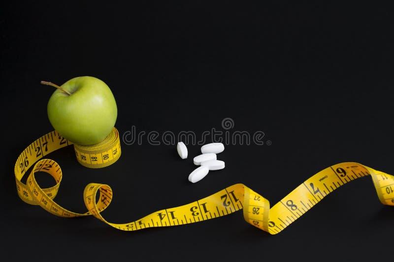 Зеленые корки яблока, белых и измеряя лента с сантиметрами и дюймами изолированные на черной предпосылке стоковые изображения