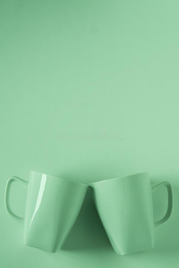 Зеленые кружки кофе на зеленой предпосылке clinking в приветственных восклицаниях с пустым copyspace стоковая фотография rf
