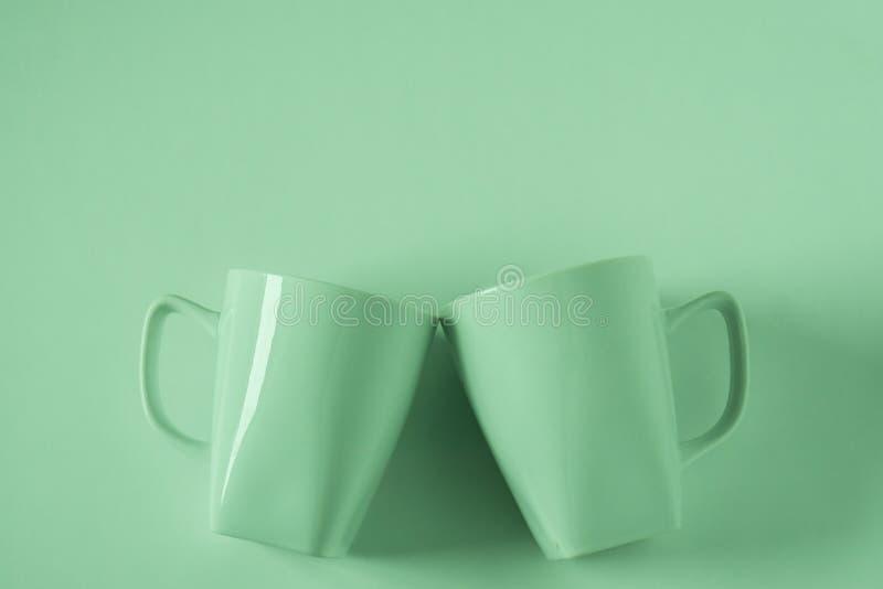 Зеленые кружки кофе на зеленой предпосылке clinking в приветственных восклицаниях с пустым copyspace стоковое фото rf