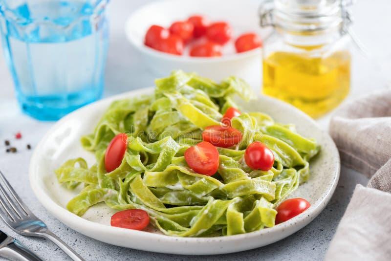 Зеленые макаронные изделия шпината в сметанообразном соусе с томатами стоковые фото