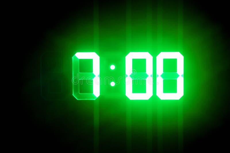 Зеленые накаляя цифровые часы в темном времени 7:00 шоу стоковое изображение rf