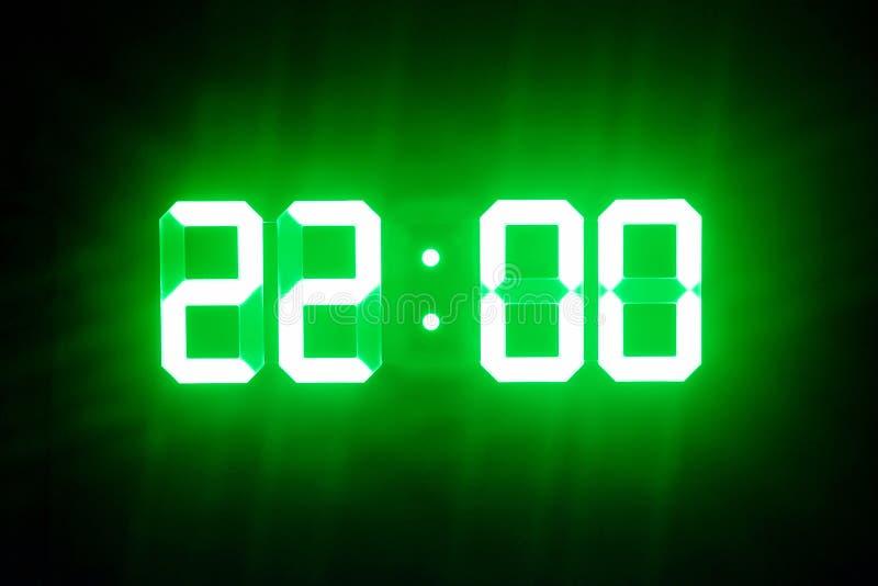 Зеленые накаляя цифровые часы в темном времени 22:00 шоу стоковая фотография