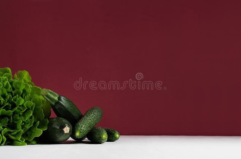 Зеленые овощи - шпинат салата, огурцы, цукини на современном красочном bordo и белый интерьер кухни стоковые фотографии rf