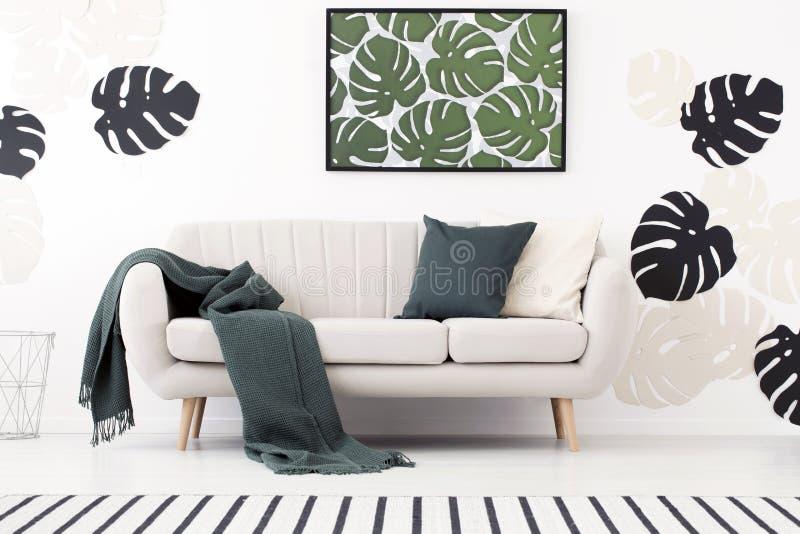 Зеленые одеяло и валик на settee в белом interio живущей комнаты стоковые изображения