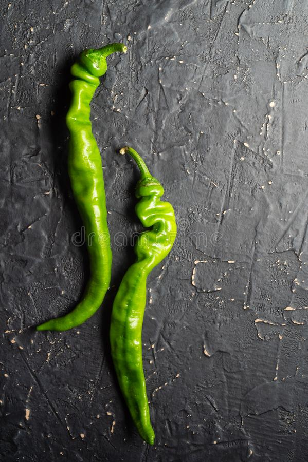 Зеленые перцы chili на черной текстурированной предпосылке стоковая фотография rf
