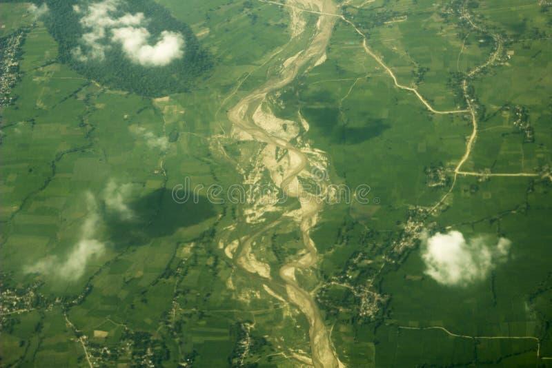 Зеленые поля и леса около русла реки с песочными банками и деревней против белых облаков воздушное strandja съемки горы Болгарии стоковое изображение
