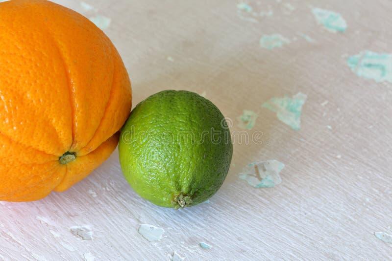 Зеленые сочные известка и апельсин На затрапезной достигшей возраста предпосылке стоковая фотография