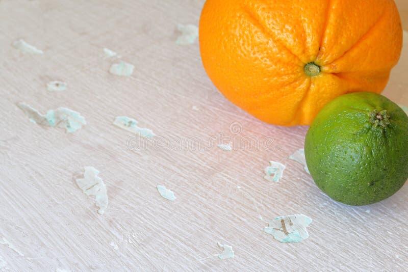 Зеленые сочные известка и апельсин На затрапезной достигшей возраста предпосылке стоковые изображения