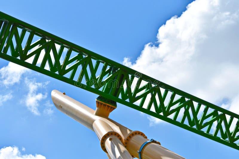 Зеленые стальные русские горки готовые для того чтобы возбудить всадники на пасмурном голубом небе на садах Буша стоковая фотография rf
