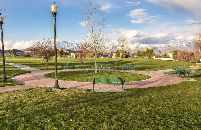Зеленые стенды вокруг круговой тропы на парке с деревьями и столбами лампы стоковое фото rf