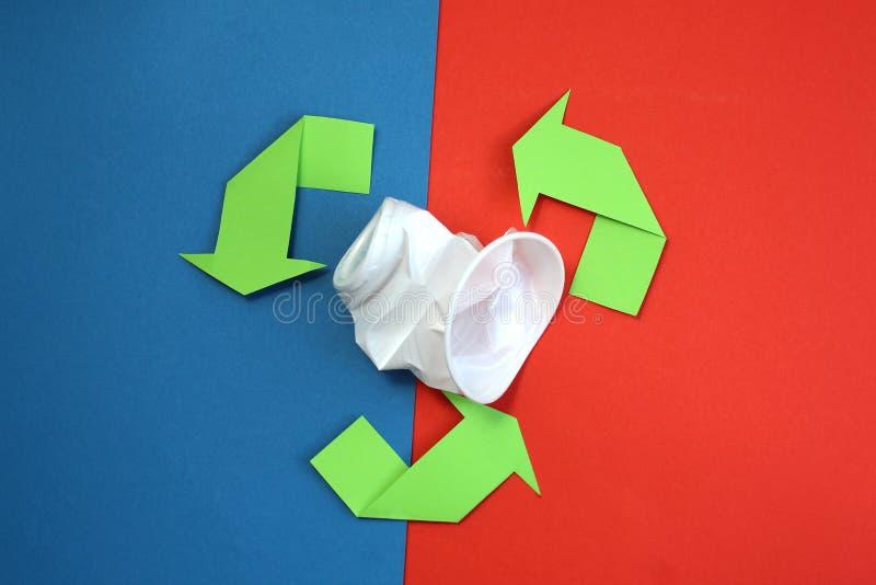 Зеленые стрелки повторно используют его символ на голубой и красной предпосылке повторно использованный материальный символ Испол стоковая фотография