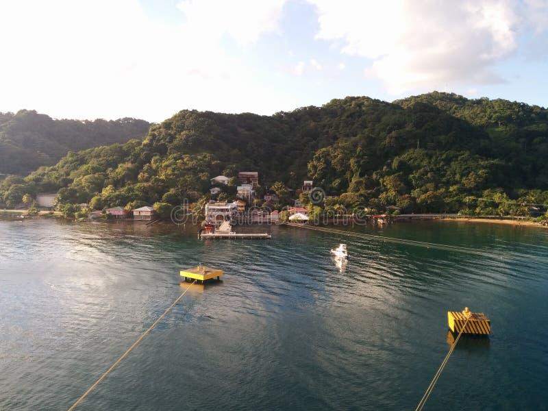 Зеленые холмы на острове подпирают с пасмурными голубым небом и морем с анкерами туристического судна стоковые фотографии rf