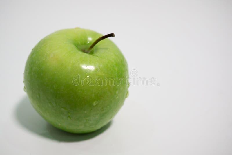 Зеленые яблоки с капельками воды на белой предпосылке стоковые изображения