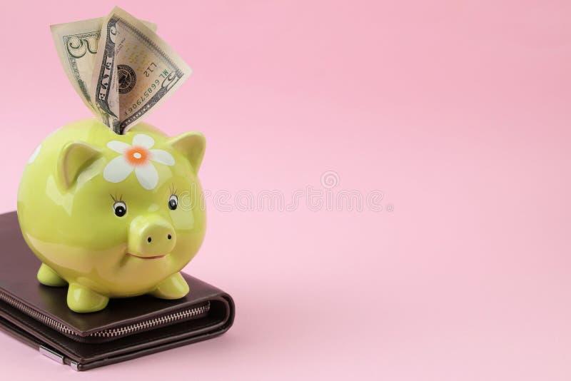 Зеленые moneybox свиньи и бумажник и деньги на яркой розовой предпосылке Финансы, сбережения, деньги E стоковое фото rf