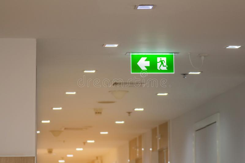Зеленый аварийный выход подписывает внутри больницу показывая путь избегать стоковое изображение rf