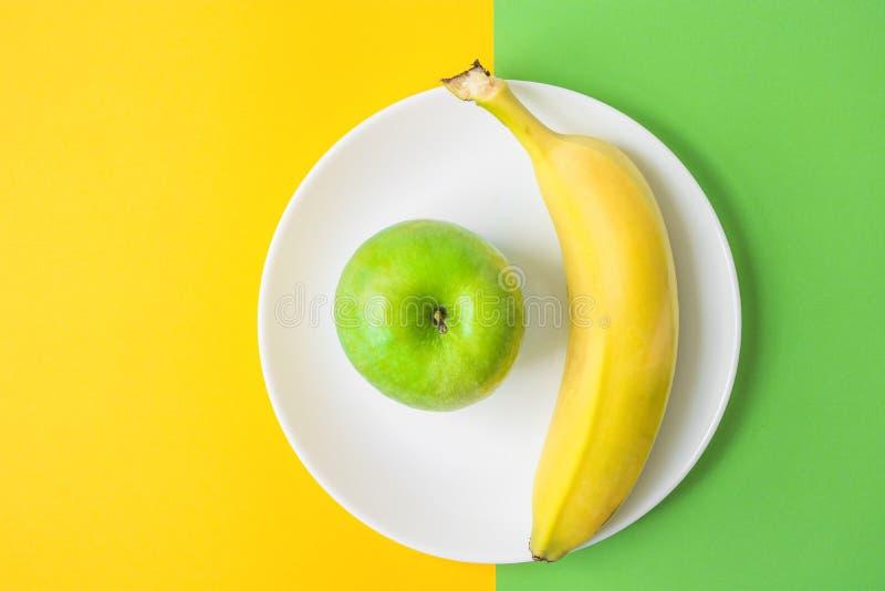 Зеленый банан Яблока на белой плите на предпосылке контраста от цветов сочетания из желтых и зеленых Здоровое питание витаминов стоковое фото rf