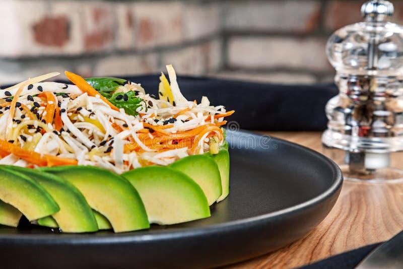 Зеленый вегетарианский обед салата с авокадоом, морковью и капустой на темной плите стоковое фото rf