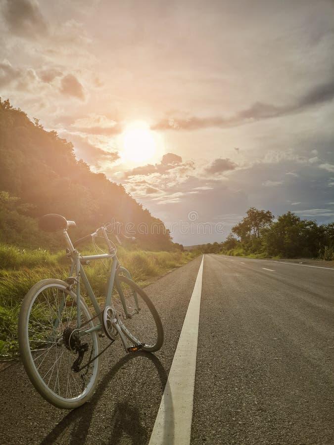 Зеленый винтажный велосипед на дороге с предпосылкой неба и захода солнца стоковое фото rf