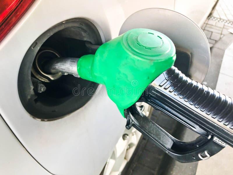 Зеленый заполняя пистолет вставил в бензобаке автомобиля на бензоколонке Процесс заполнять автомобиль с топливом, бензином, тепло стоковое фото