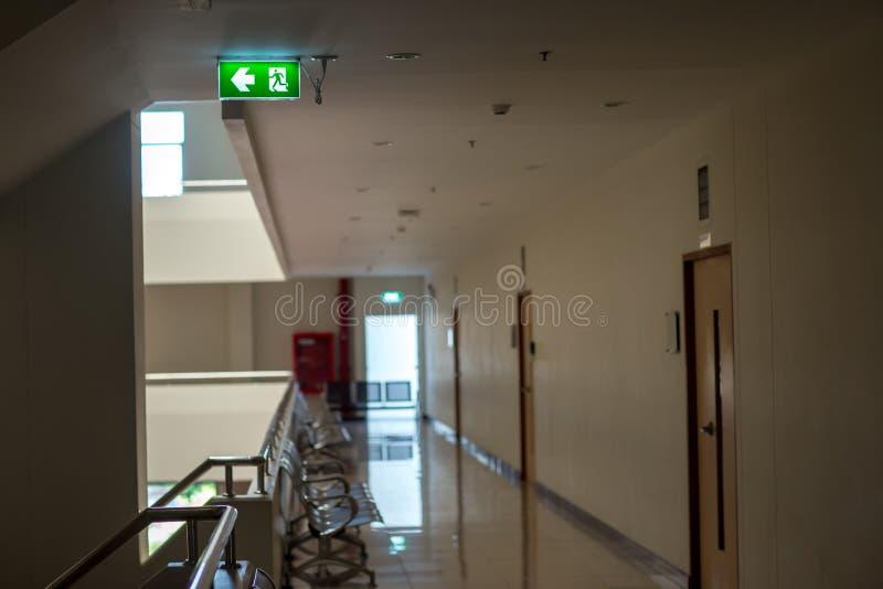 Зеленый знак аварийного выхода показывая путь избегать Пожарный выход в здании стоковая фотография