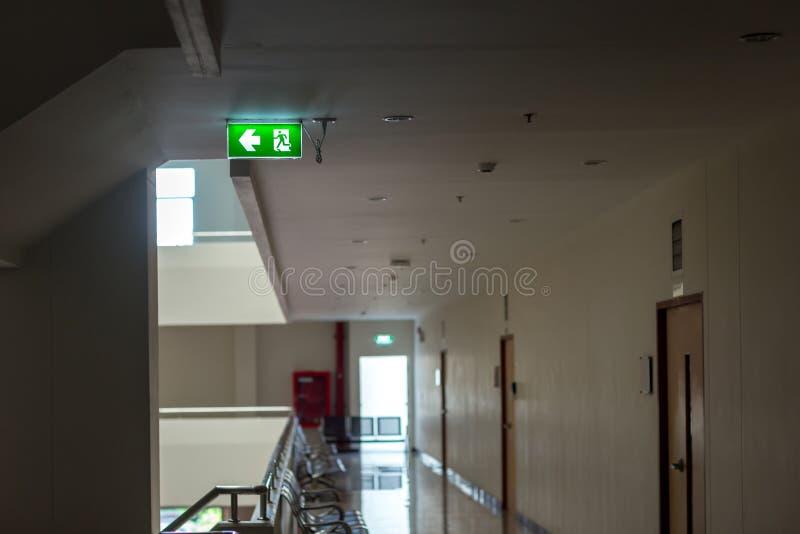 Зеленый знак аварийного выхода показывая путь избегать Пожарный выход в здании стоковые фото