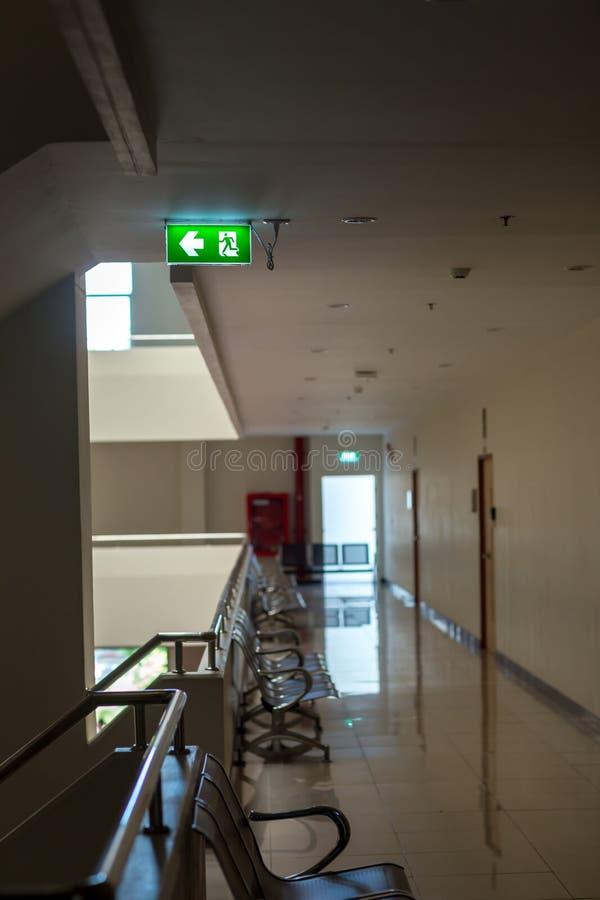 Зеленый знак аварийного выхода показывая путь избегать Пожарный выход в здании стоковые изображения rf