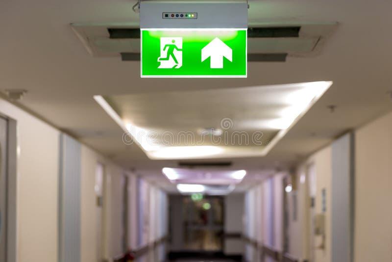 Зеленый знак аварийного выхода показывая путь избегать Пожарный выход в здании стоковое фото