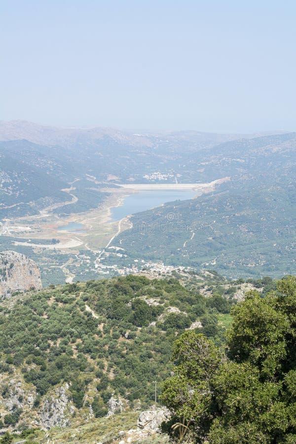 Зеленый и голубой ландшафт с озером, зелеными деревьями и горами стоковое изображение