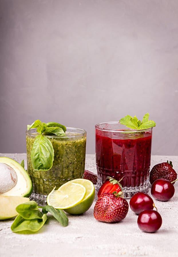 Зеленый и красный smoothie клубники, сладкой вишни, авокадоа, шпината, базилика, известки, зеленого яблока на серой предпосылке стоковое изображение