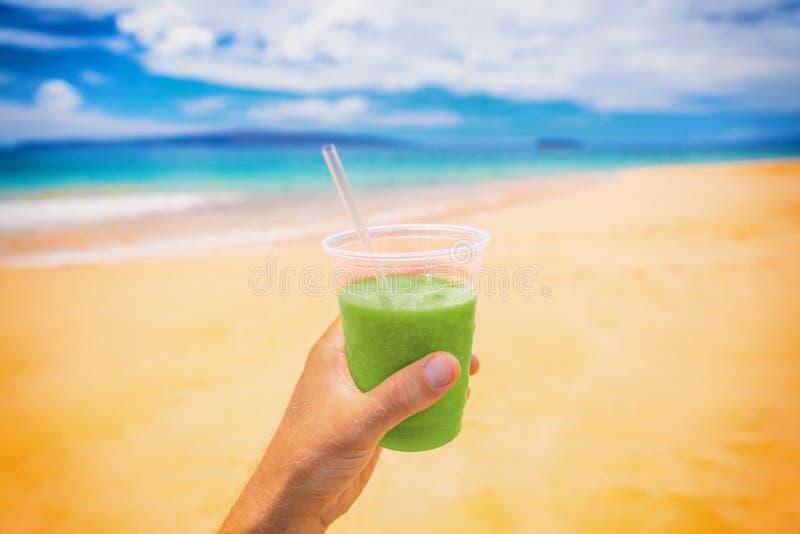 зеленый коктейль detox напиток селфи человек держащий пластиковую чашку на пляже летний фон Картина здорового питания стоковое изображение rf