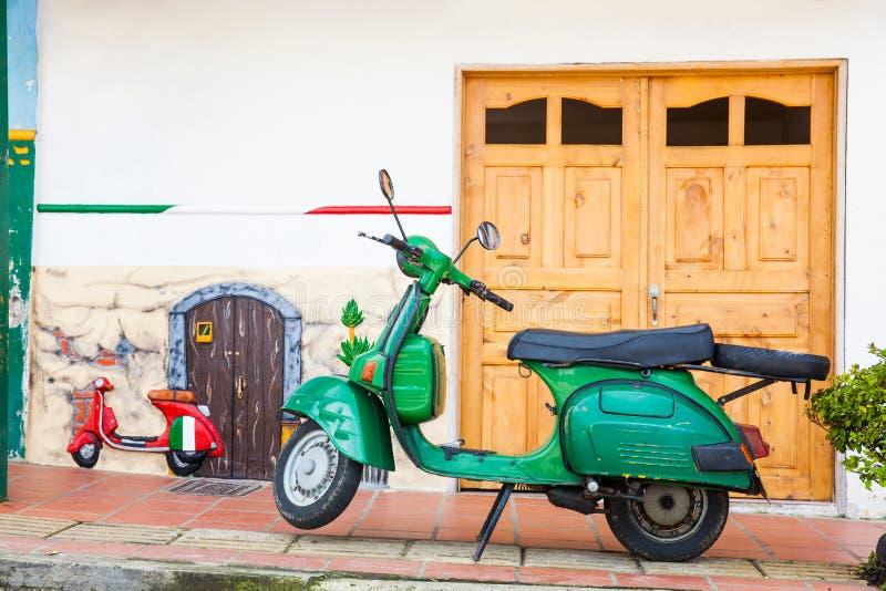 Зеленый мотоцикл на красочном городке Guatape, Antioquia стоковые фотографии rf